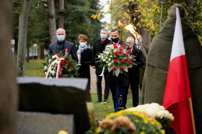 Burmistrz Mateusz Feder wraz ze starostą Bogusławem Kierusem podczas składania kwiatów na strzeleckim cmentarzu.